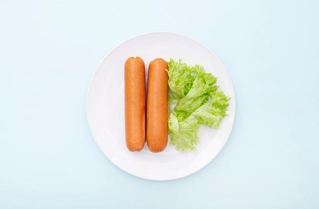 Gekookte worst op witte keramische plaat met groen, ochtendontbijt, bovenaanzicht, lay-out