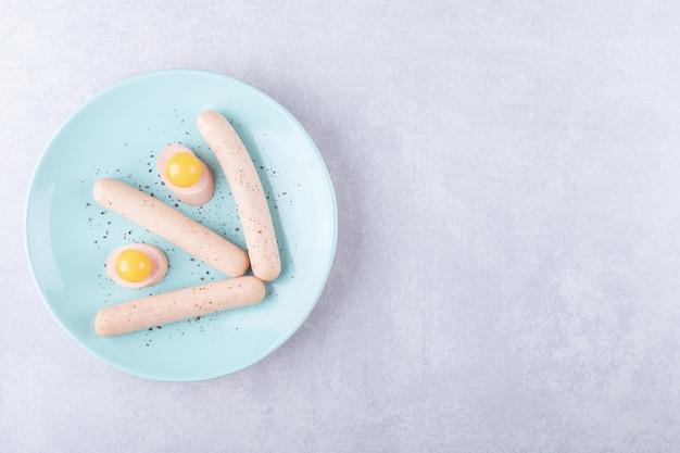Gekookte worstjes en eigeel op blauw bord.