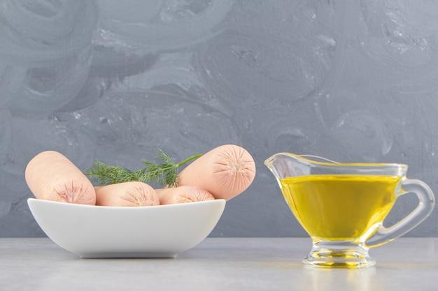 Gekookte worstjes in witte kom met olijfolie.