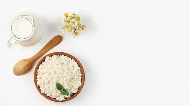 Gekorrelde kwark in een aarden kom, naast houten lepel en kruik melk. lay-out op heldere witte achtergrond met kopie ruimte. zachte kwark, natuurlijke gezonde voeding, complete dieetvoeding