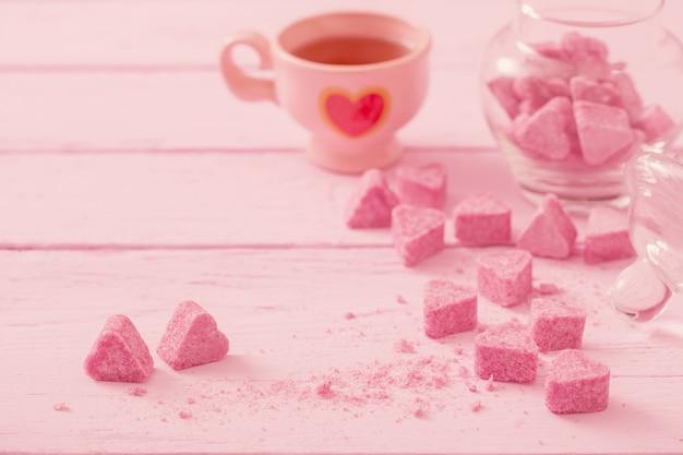 Gekorrelde roze suiker in de vorm van hart en kopje thee op een houten achtergrond