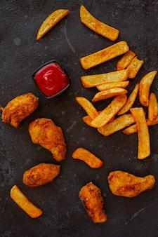 Gekruide franse aardappelen en gebakken kip met ketchup op een donkere achtergrond