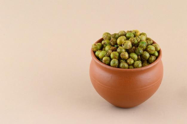 Gekruide gebakken doperwten {chatpata matar} indiase snack. gedroogde gezouten groene erwten in aarden pot.