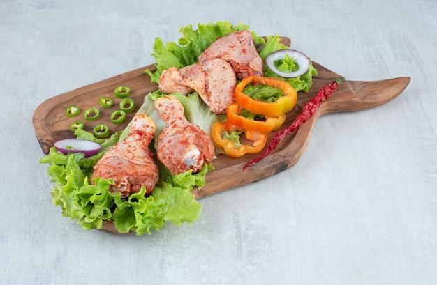 Gekruide kipdelen met groenten op een houten bord.