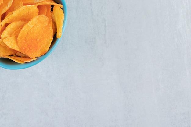 Gekruide knapperige chips in blauwe kom op steen.