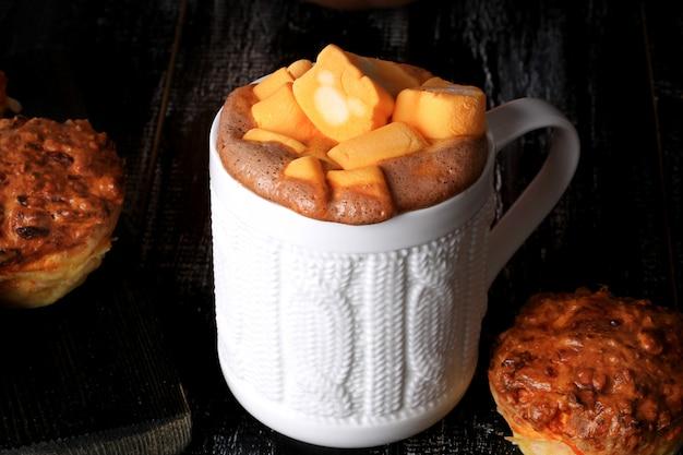 Gekruide pompoenkoffie met marshmallows en pompoenmuffins op een zwarte houten achtergrond