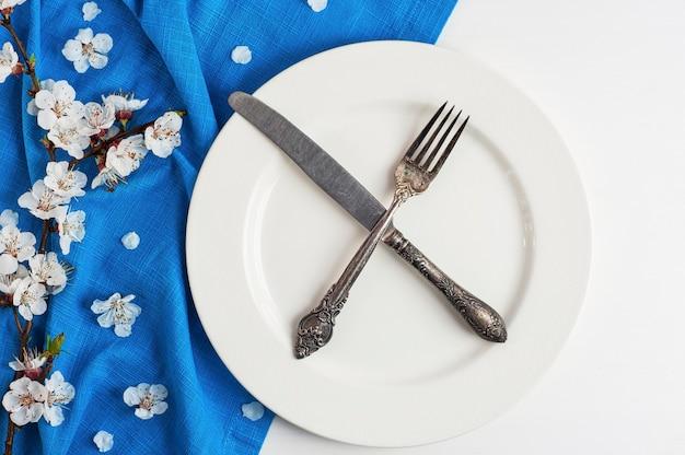 Gekruist mes en vork op een lege witte plaat