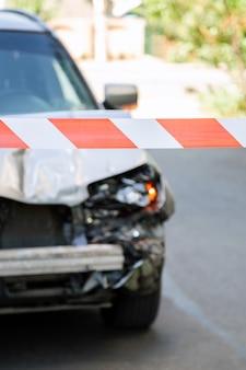 Gekruiste rood-witte waarschuwingsband voor auto-ongeluk. gebroken motorkap van auto op weg omheind door rode waarschuwingstape. gebroken bumper en autokoplampen met licht op wegdekasfalt met niemand.