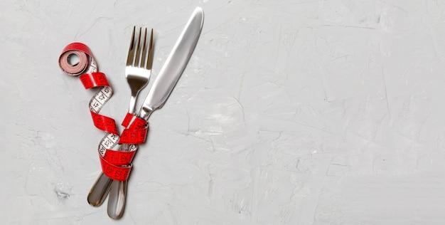 Gekruiste vork en mes zijn verpakt in meetlint op grijs.