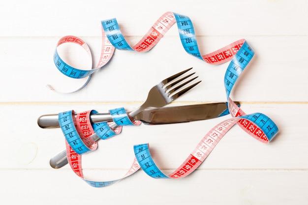 Gekruiste vork en mes zijn verpakt in meetlint op houten achtergrond.