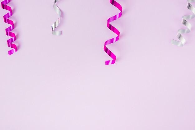 Gekruld roze en zilveren slingers op de top van roze achtergrond