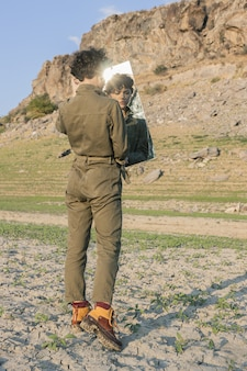 Gekruld stijlvol model met een bruine jumpsuit in de spiegel kijkend met een verwarde uitdrukking