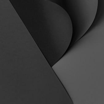 Gekruld zwart kaartpapier op een donkergrijze achtergrond
