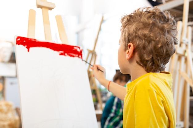Gekrulde blonde jongen kleurend papier met rood
