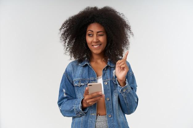 Gekrulde donkere dame in vrijetijdskleding die wijsvinger opsteekt terwijl ze een idee heeft, vrolijk glimlacht en één oog gesloten houdt, poserend over witte muur met smartphone in de hand