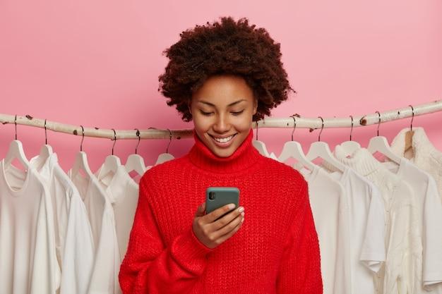 Gekrulde harige vrolijke vrouw met blije uitdrukking, gebruikt mobiele telefoon om online te betalen, gekleed in een rode trui, staat tegen kledingvodden, geïsoleerd op roze achtergrond.