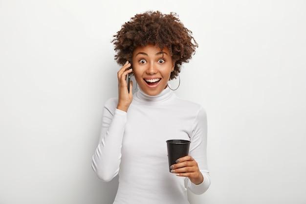 Gekrulde harige vrouw heeft een gelukkig gesprek via smartphone, geniet van grappig nieuws luisteren, houdt zwart papier kopje drankje