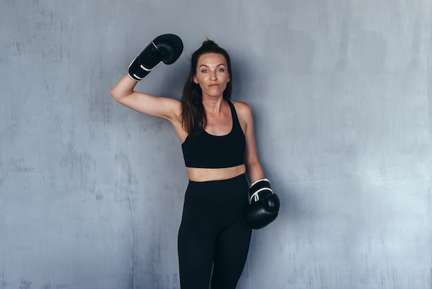 Gekscherende vrouw in bokshandschoenen dreigt met haar vuist.