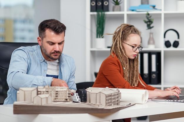 Gekwalificeerde hardwerkende creatieve mannelijke en vrouwelijke ontwerpers die werken met mock-up van gebouwen en blauwdrukken op laptop.
