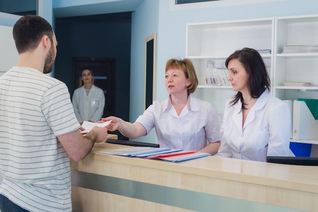 Gekwalificeerde lachende artsen werken met de klant bij de receptie in het ziekenhuis