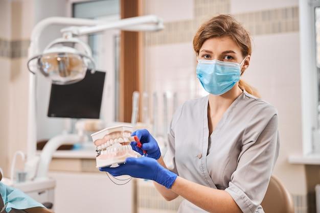 Gekwalificeerde vrouwelijke tandarts die persoonlijke beschermingsmiddelen draagt tijdens het tonen van reinigingstechnieken in mondhygiëne