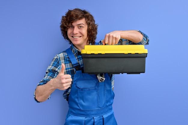 Gekwalificeerde werkman in overall met instrumenten geïsoleerd op paarse achtergrond