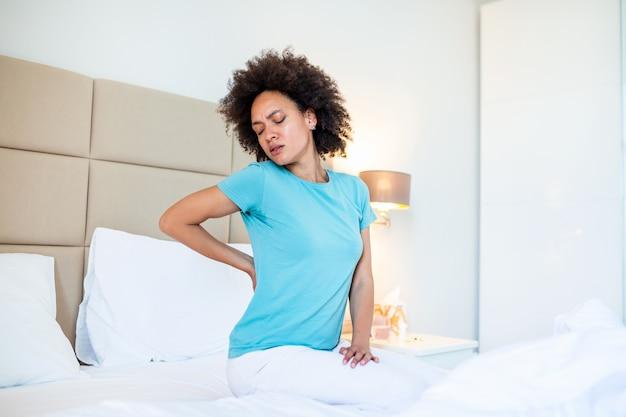 Gekwetst afro-amerikaanse jonge vrouw zitten in het witte bed wakker worden met aanrakingen terug lijden aan pijnlijke rugpijn