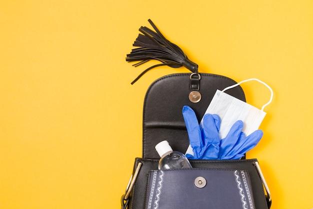 Gel-alcoholdesinfecterend middel, gezichtsmasker en blauwe rubberen wegwerphandschoenen in een handtas op een gele achtergrond