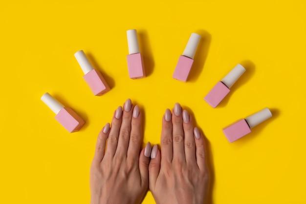 Gel polish van roze kleur en handen met manicure op een gele achtergrond
