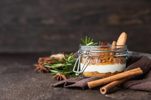 Gelaagd dessert in glazen pot met koekkruimel en slagroom gedecoreerd met rozemarijn en anijs, donkerbruin oppervlak