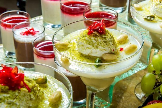Gelaagd mascarponedessert met gemalen vanillekoekjes, vijgen en amandelen in een glazen pot
