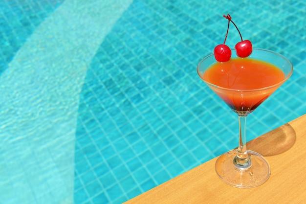 Gelaagde alcoholische cocktail met kersen aan de rand van het buitenzwembad.