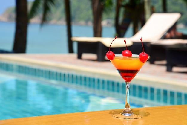 Gelaagde alcoholische cocktail met kersen aan de rand van het buitenzwembad