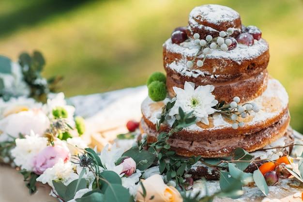 Gelaagde cake versierd bloemen op feestelijke tafel