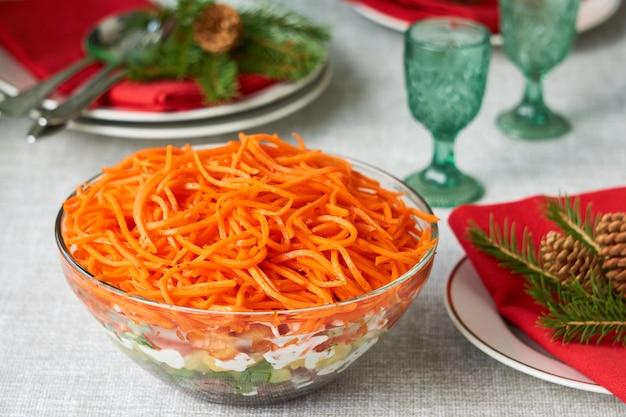 Gelaagde groentesalade met koreaanse wortelen in een glazen kom