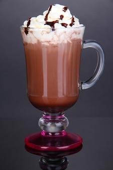 Gelaagde koffie in glas op tafel op grijs