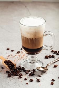 Gelaagde koffiemoccacino met chocolade in een glazen mok op het betonnen oppervlak