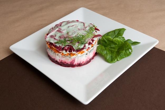 Gelaagde shuba-salade met biet, aardappel, wortel, zure haring en mayonaise.