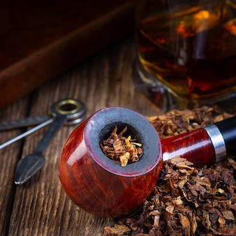 Gelakte rookpijp en tabakstapel