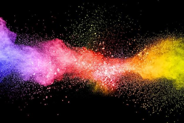 Gelanceerd kleurrijk poeder op zwarte achtergrond. de explosie van het kleurenpoeder het kleurrijke bespatten van het stof.