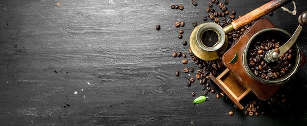 Gelaste koffie in een turks met een handmolen. op het zwarte bord.