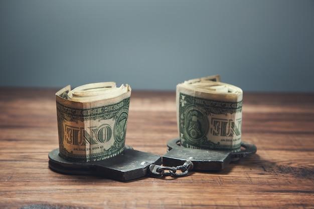 Geld aan de handboeien op de tafelachtergrond
