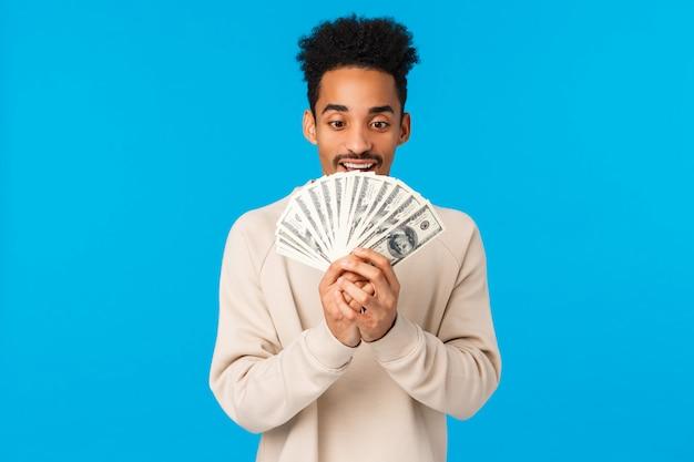 Geld altijd zonnig. opgewonden en gelukkig afro-amerikaanse man op zoek naar contant geld met verleiding en vreugde, droomt wat kopen als winnende loterij, kreeg verhoging, staande blauwe muur