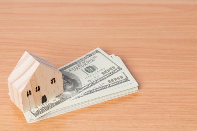 Geld amerikaanse dollars met een houten huismodel op houten achtergrond.