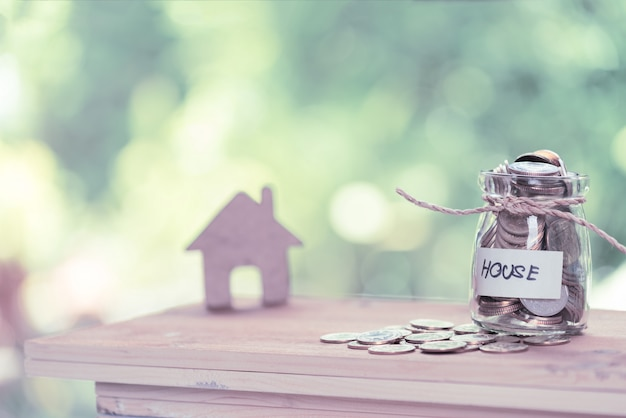 Geld besparen voor huis, munten in glazen pot met citaat huis op houten tafel