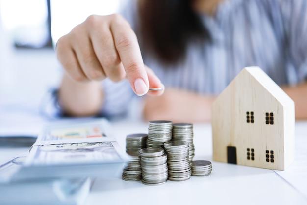 Geld besparen voor investeringen in onroerend goed met stapel geldmunten voor het kopen van een huis en een lening ter voorbereiding in het toekomstige financiële of verzekeringsconcept
