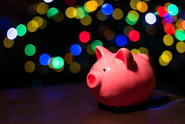 Geld besparen voor kerstcadeau. vakantie spaarvarken met kleurrijke bokeh ballen op de achtergrond.