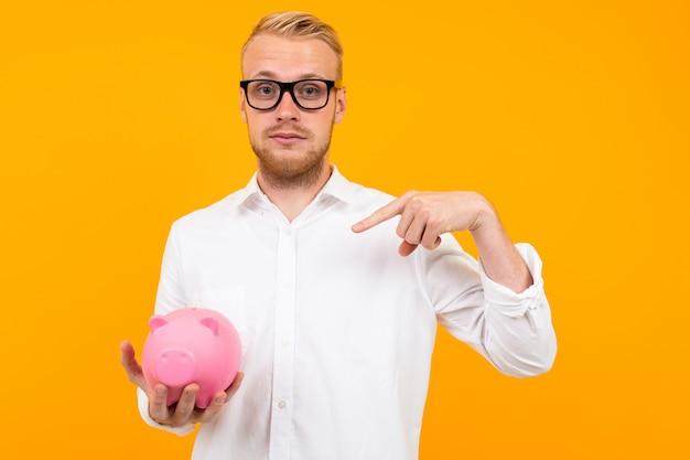 Geld concept. aantrekkelijke charmante blonde man in een klassiek shirt met een bril heeft een spaarpot op geel