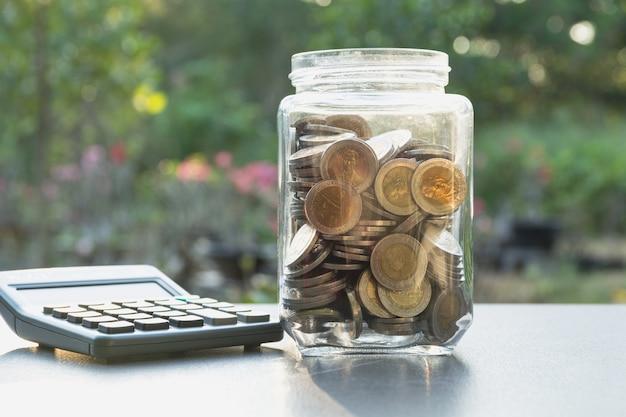 Geld concept opslaan met geld munten in de pot en rekenmachine voor het bedrijfsleven