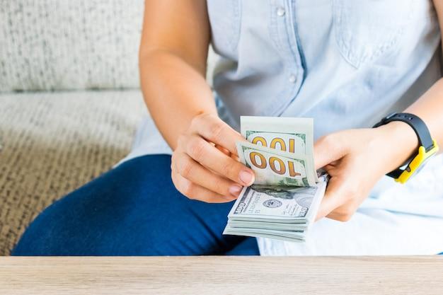 Geld concept opslaan. vrouw het tellen van dollars aan tafel.